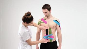 terapista femminile che applica nastro kinesiologico sull'addome di un uomo sullo sfondo chiaro. la donna prepara il paziente maschio per incollare il nastro adesivo kinesio sulla pancia foto
