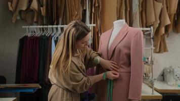 primo piano del designer su misura femminile sta delineando l'abbigliamento appuntato al manichino sartoriale con nastro di misura. la donna è concentrata e premurosa. lo studio è moderno, con molti strumenti e oggetti per cucire. foto
