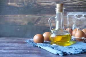 primo piano di uova in una ciotola e olio da cucina sul tavolo foto