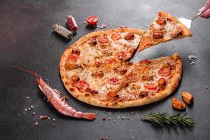 gustosa pizza a fette con frutti di mare e pomodoro su fondo di cemento foto