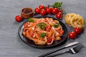 fettuccine con gamberi, pomodorini, salsa, spezie ed erbe aromatiche foto