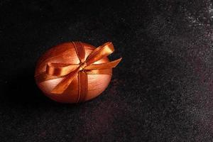 uovo di Pasqua con nastro regalo su uno sfondo di legno scuro foto