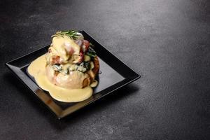 uova alla Benedict o uova alla fiorentina su un piatto nero al bar foto