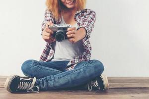 giovane fotografo hipster donna che prende foto e guarda la fotocamera