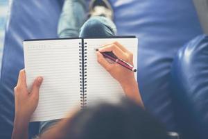 mani della donna che scrivono sul blocco note che si trova a casa. foto