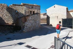 donna con zaino che cammina attraverso il villaggio medievale foto
