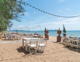 sedie bianche e tavolo sulla spiaggia con vista sull'oceano blu e cielo limpido: migliora lo stile di elaborazione del colore e dell'illuminazione foto