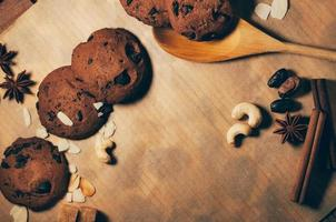 biscotti rotondi croccanti al cioccolato con cucchiaio di legno e spezie foto