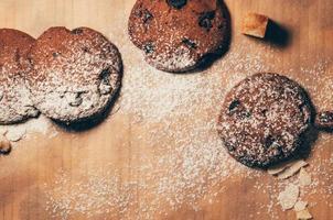 vista dall'alto di biscotti al cioccolato infarinati sul tavolo foto