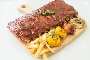 costata di maiale alla griglia con salsa barbecue e verdure e patatine fritte foto