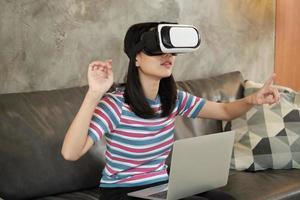 donna asiatica con auricolare vr, guardando la simulazione virtuale 3d. foto
