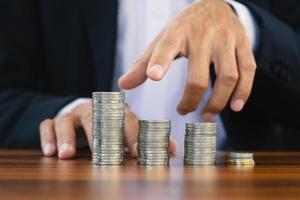 pila di monete contando a mano sul tavolo di legno foto