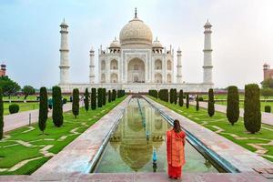 Una donna in piedi davanti al Taj Mahal, un mausoleo di marmo bianco avorio sulla riva sud del fiume Yamuna ad Agra, Uttar Pradesh, India. una delle sette meraviglie del mondo. foto