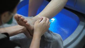 stazione termale del piede. piedi nudi della donna che massaggiano nella macchina dell'acqua saponosa al negozio della stazione termale. foto
