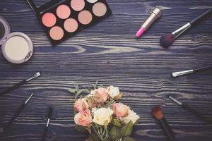 vista dall'alto una collezione di trucco cosmetico e fiori su un tavolo di legno foto