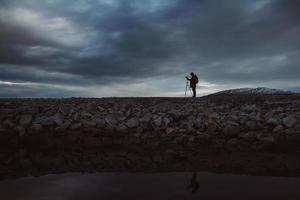 sagoma di un fotografo o viaggiatore con treppiede in piedi su pietra foto