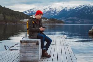uomo viaggiatore che guarda nel telefono seduto sul molo di legno foto
