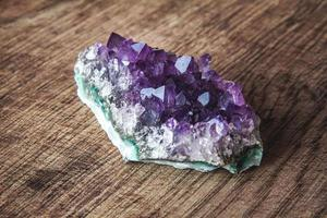 cristallo di ametista viola su uno sfondo di legno foto