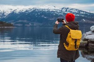 uomo viaggiatore che scatta foto con lo smartphone sulle montagne