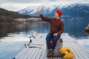uomo viaggiatore che scatta un autoritratto con uno smartphone foto