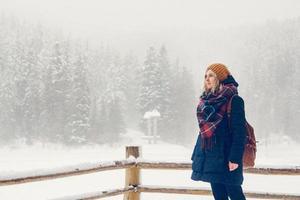 la ragazza sta facendo una passeggiata attraverso una fitta foresta durante una giornata invernale foto