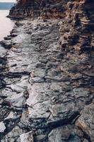 trama di una spiaggia rocciosa vicino all'acqua. sfondo di mucchio di roccia foto