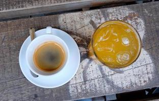tazza di caffè e un bicchiere di succo d'arancia fresco su una tavola di legno foto