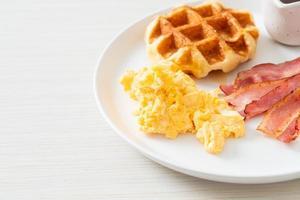 uova strapazzate con bacon e waffle a colazione foto