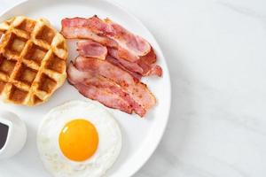 uovo fritto con bacon e waffle per colazione foto