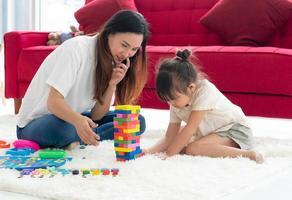 madre asiatica che insegna alla sua giovane figlia a giocare a puzzle a casa foto
