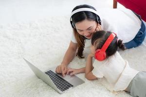 madre asiatica con bambino che insegna a studiare dal computer a casa foto