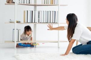 ragazza asiatica che gioca a nascondino con la madre in soggiorno foto