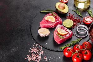 Bistecche di filetto di tonno fresco con spezie ed erbe aromatiche su sfondo nero foto