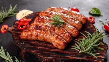 salsicce alla griglia con verdure e spezie su sfondo nero foto
