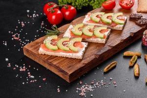 delizioso panino fresco con pesce rosso, burro, pane e avocado foto