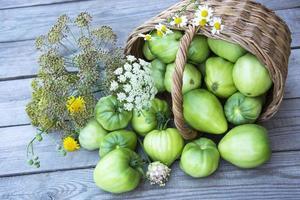 verdure in un cesto di vimini su uno sfondo di legno foto