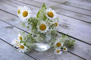 bellissimi fiori di campo fiori soleggiati su uno sfondo di legno foto