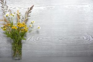 un mazzo di fiori di campo in un vaso di vetro su un tavolo di legno con un posto vuoto per il testo foto