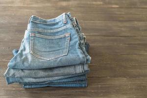 pile di vestiti di jeans su fondo di legno foto