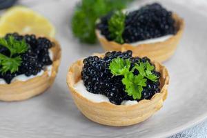 caviale nero in tartellette su sfondo chiaro. concetto di cibo sano. foto