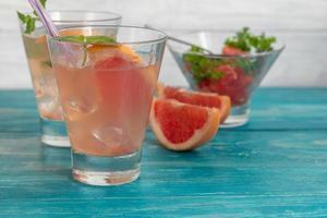 cocktail al pompelmo su fondo chiaro con un rametto di menta foto
