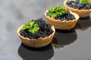 caviale nero in tortine su uno sfondo scuro. concetto di cibo sano. foto