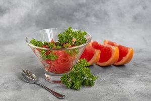 insalata estiva con pompelmo su sfondo chiaro con erbe aromatiche. foto