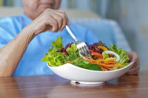 paziente asiatico senior della donna che fa colazione all'ospedale? foto