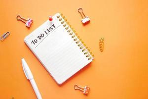 lista delle cose da fare nel taccuino con i fornitori dell'ufficio su sfondo arancione. foto