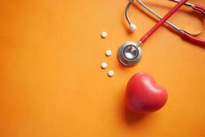 simbolo a forma di cuore e stetoscopio su sfondo arancione foto