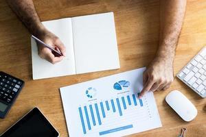 contabilità e manager che scrivono su carta e guardano il grafico finanziario foto