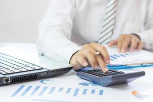 l'uomo d'affari preme la calcolatrice e controlla il grafico commerciale in carta foto