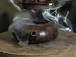 la mano maschio del primo piano apre il coperchio di una teiera dell'argilla fatta foto
