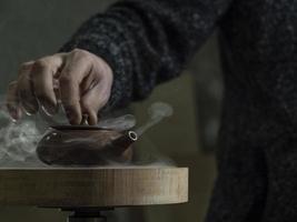la mano maschile ha chiuso il coperchio di una teiera di argilla fatta di argilla yixing foto